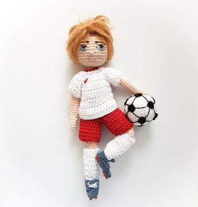 Tomek - piłkarz - chłopiec (lala) na szydełku wykonany metodą amigurumi, z piłką nożną i w piłkarskim, zdejmowanym ubranku